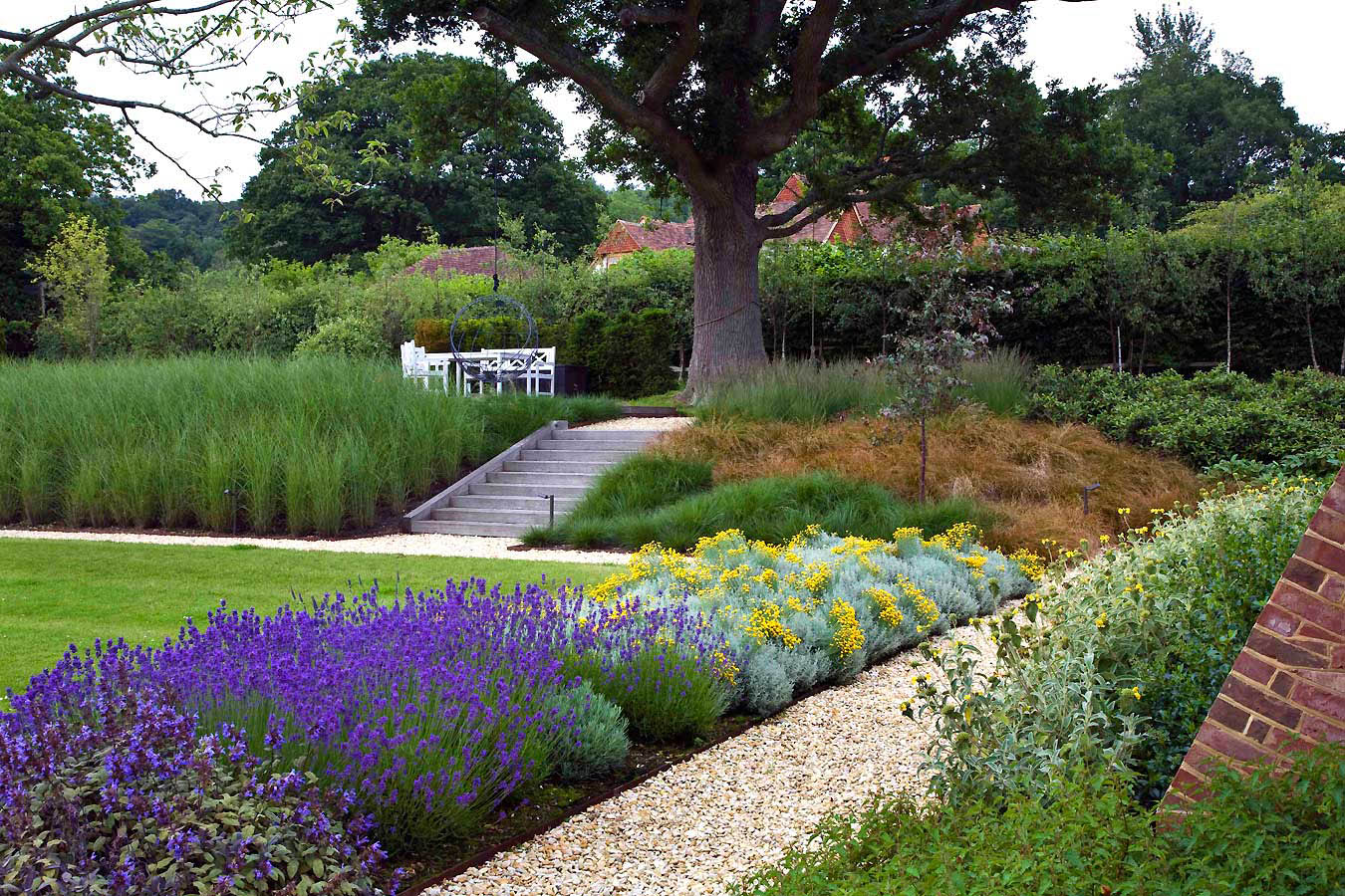 Gravel pathway and stone steps with bold drifts of colourful planting and mature trees. Rae Wilkinson Garden and Landscape Design.