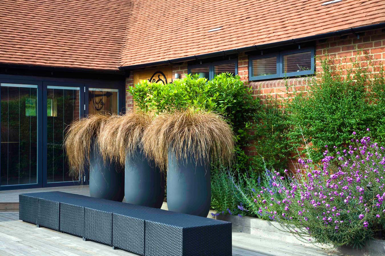 Specimen grasses in three tall planters next to a seat by the stable buildings. Rae Wilkinson Garden and Landscape Design - Garden Designer Sussex, Surrey, London, South-East England