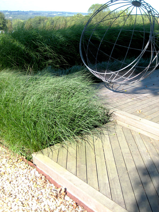 Detail of timber sundeck with foreground grasses. Rae Wilkinson Garden and Landscape Design - Garden Designer Sussex, Surrey, London, South-East England