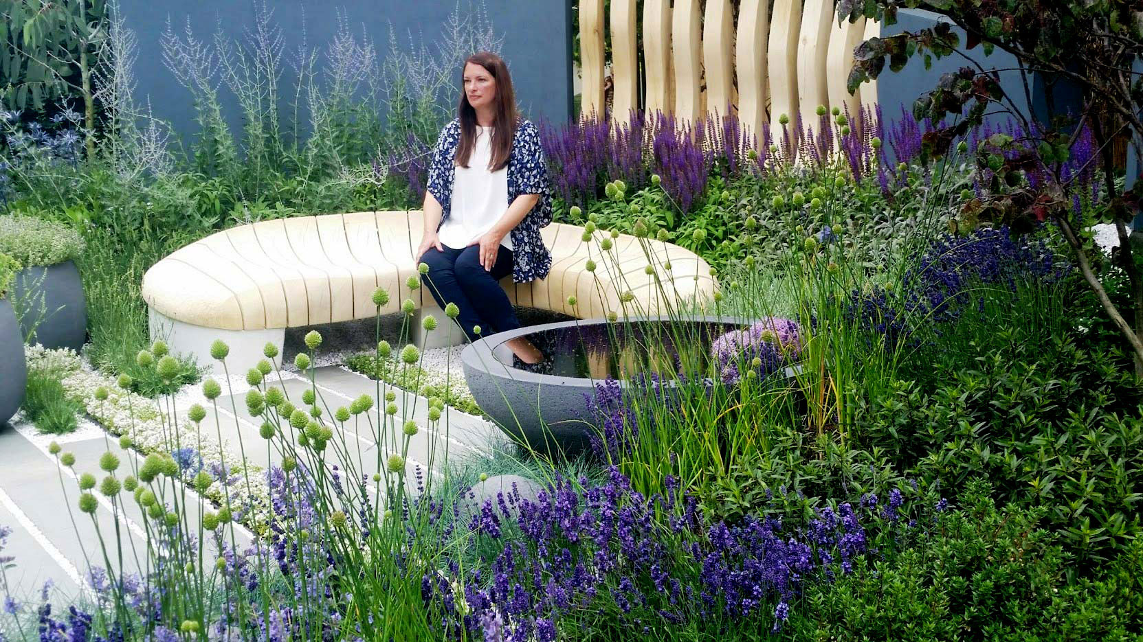 Rachel de Thame sitting in Rae Wilkinson's RHS Hampton Court garden. Rae Wilkinson Garden and Landscape Design - Garden Designer Sussex, Surrey, London, South-East England