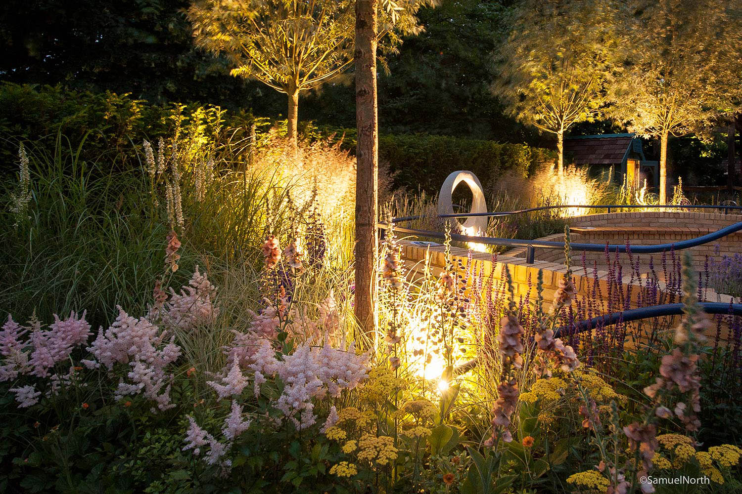 Rae Wilkinson Show Garden with evening lighting. Rae Wilkinson Garden and Landscape Design - Garden Designer Sussex, Surrey, London, South-East England