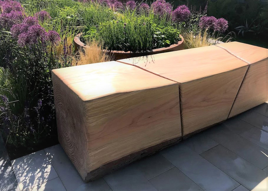 Rae Wilkinson's Chelsea Show Garden with detail of bespoke wooden bench. Rae Wilkinson Garden and Landscape Design - Garden Designer Sussex, Surrey, London, South-East England